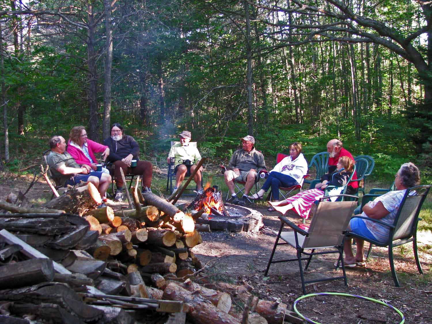 The group picks up around the fire for morning coffee